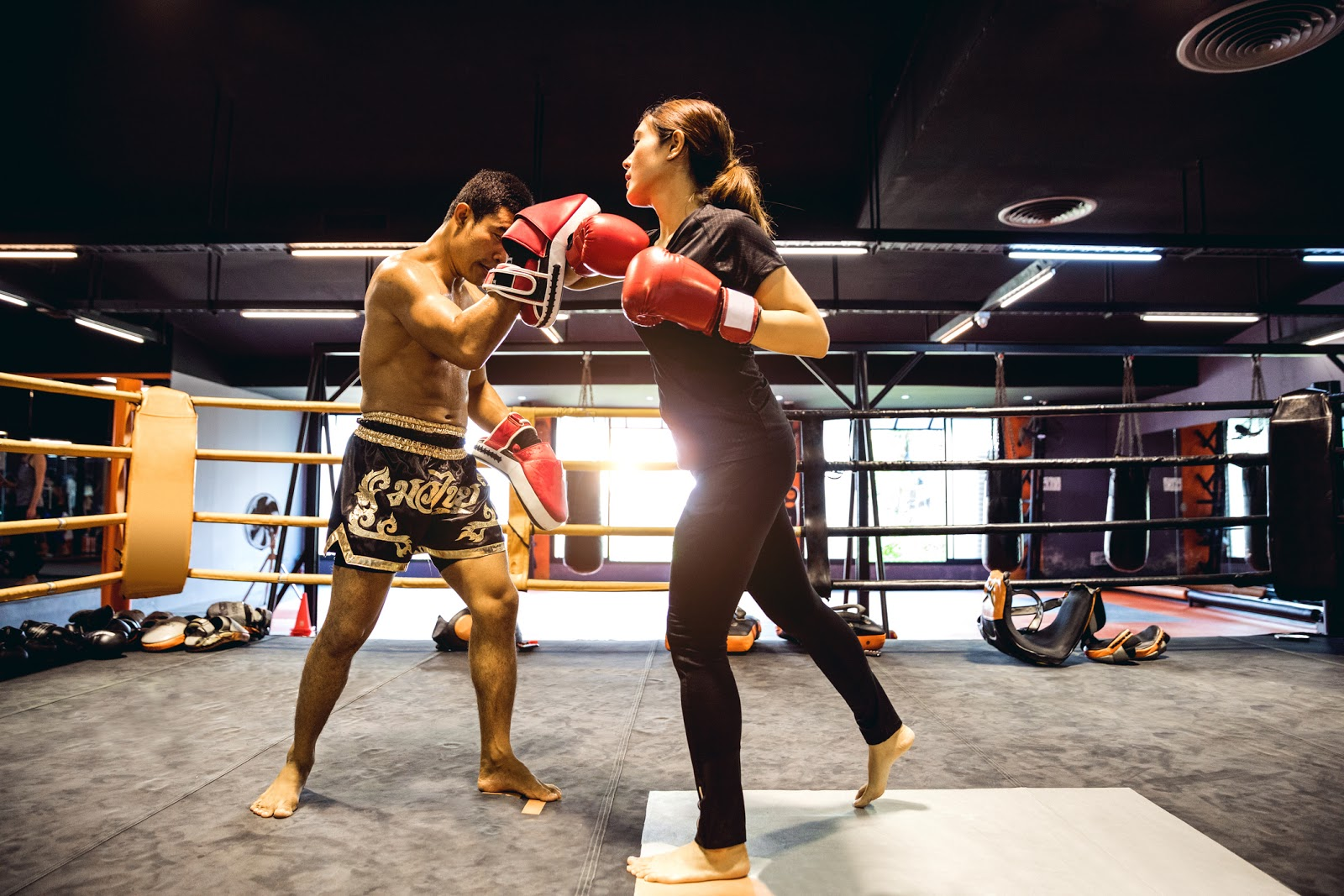 Man training a woman using punch pads in a boxing gym.