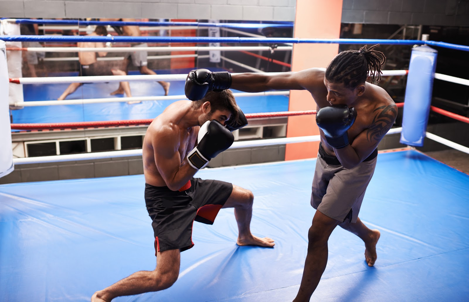 Boxer evading a punch long reach punch with his guard up in a training ring