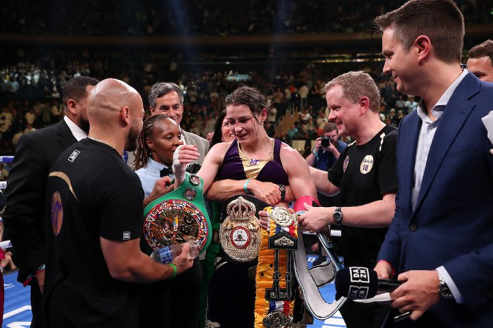 Katie Taylor surrounded by Boxing WBC officials and carrying all for lightweight world championship belts.