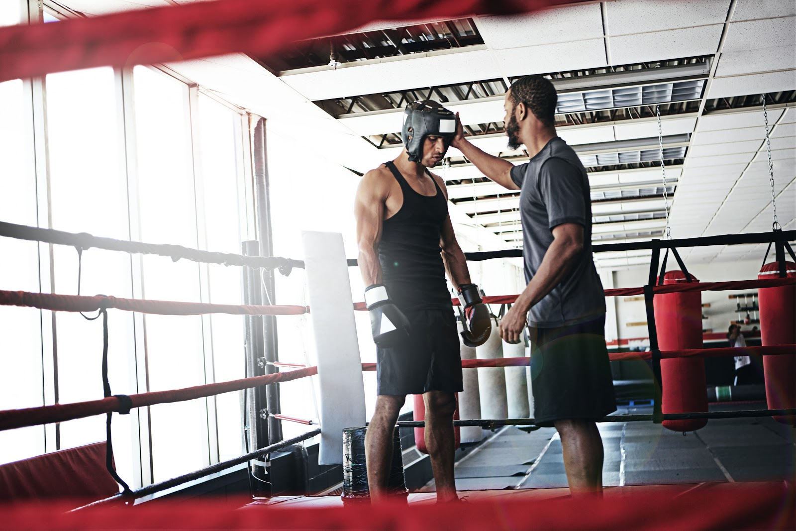 Boxing trainer instructing boxer in the ring to use head.