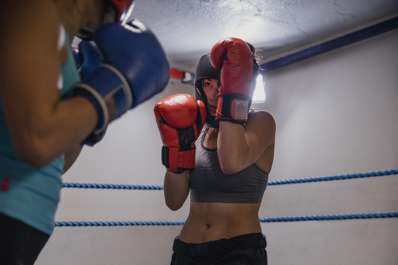 Two female boxers sparring and training with a high guard to block attacks.