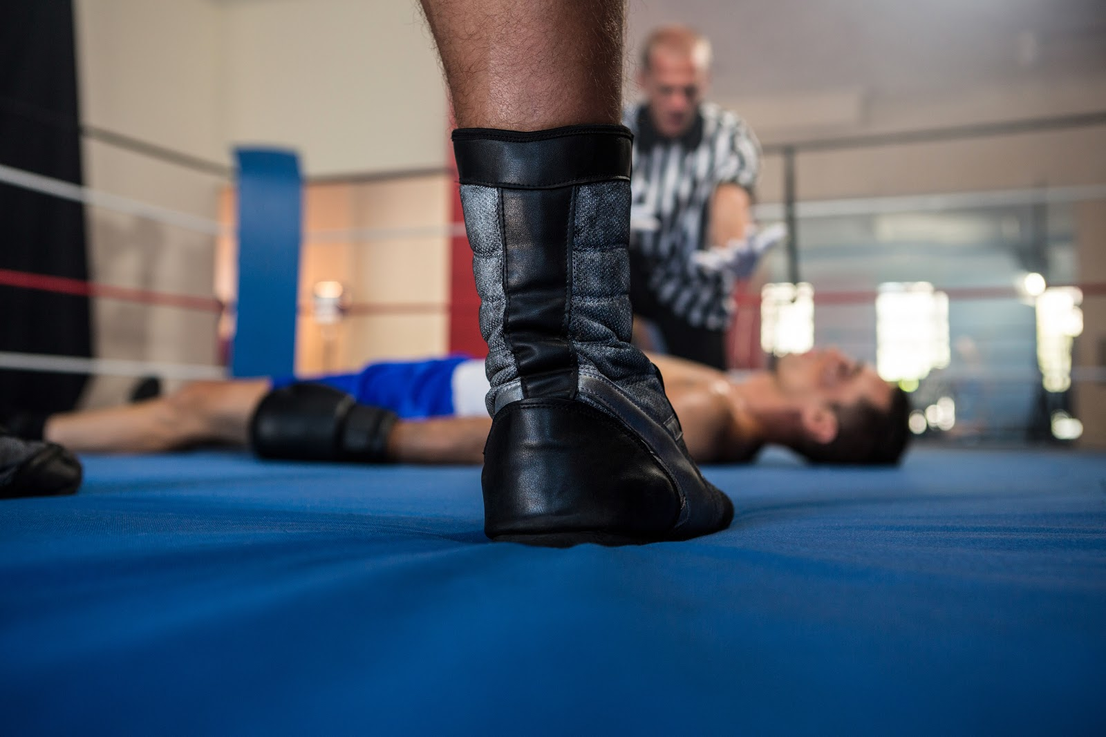 Boxing referee counting down a knockout in a ring.
