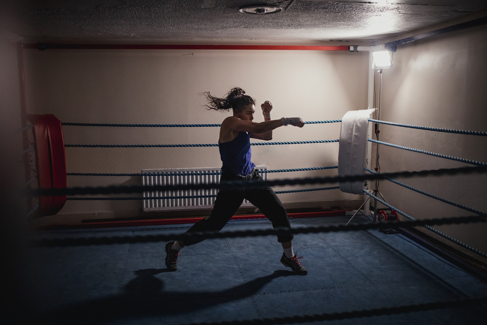 Strong woman training hard and solo using shadow boxing in dimly lit boxing ring.