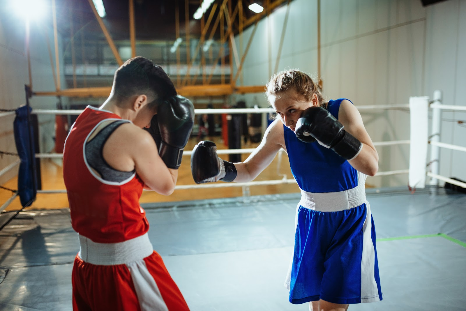 Two female boxers in the ring in action one on the offence and one with high guard.