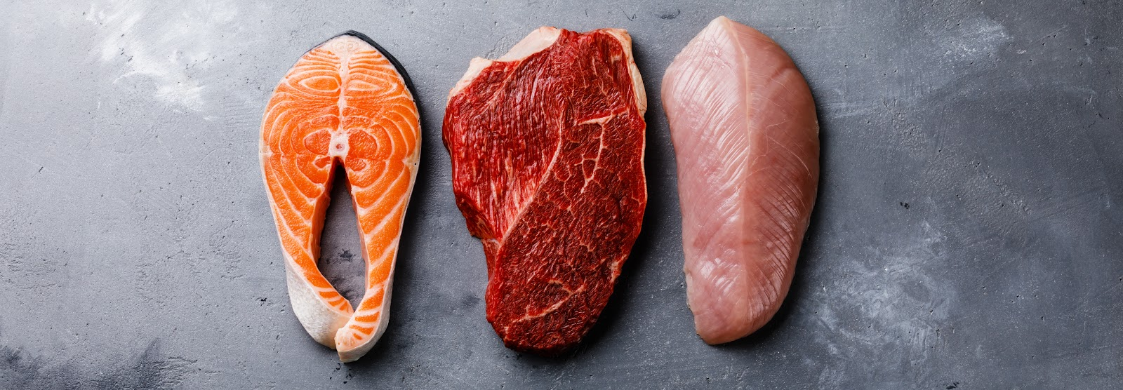A salmon, steak and chicken cut on steel counter.