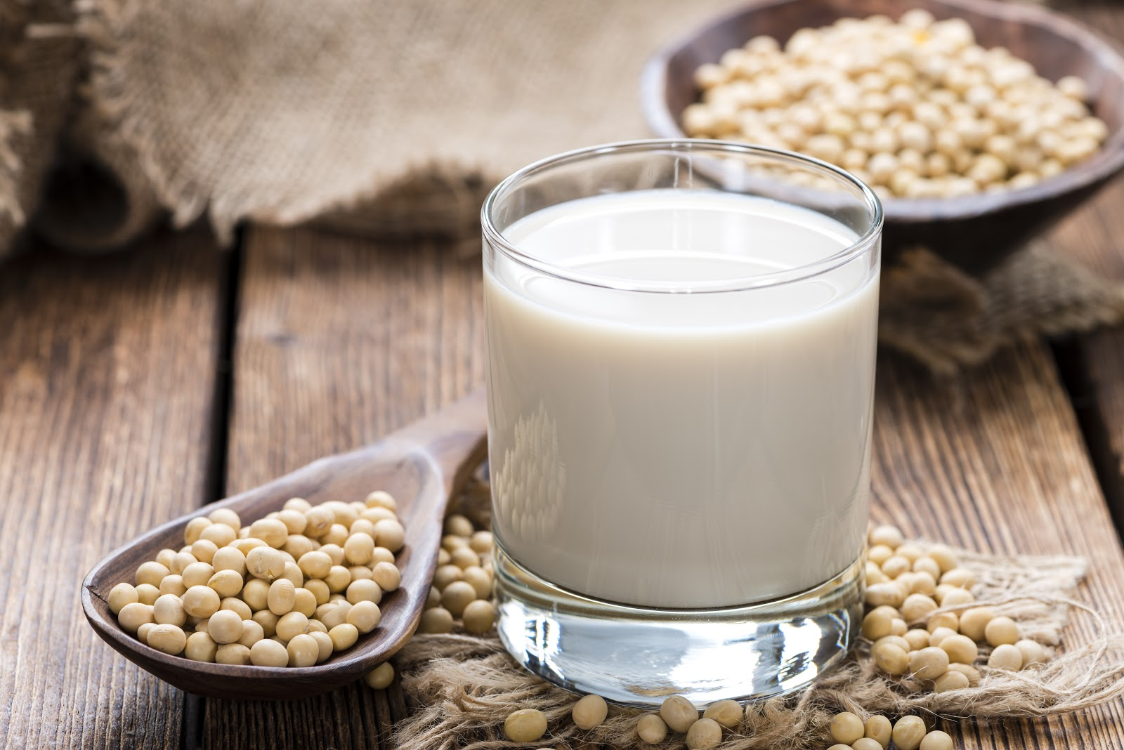 A glass of soy milk with soy beans arranged on a wooden spoon around the glass.