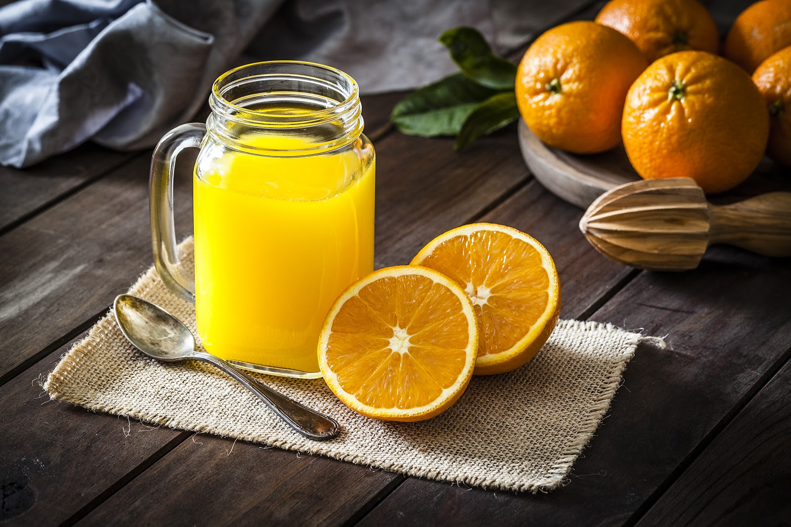 Orange juice in a mason glass with an orange cut in half and wooden orange squeezer.