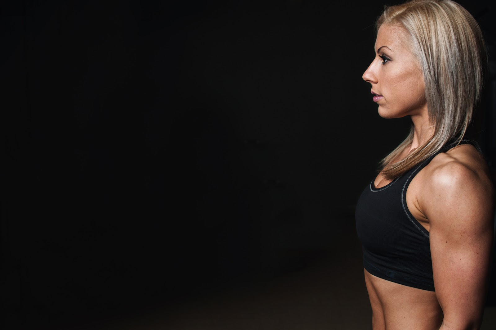 Side view of strong, fit woman against black background looking focused and determined.
