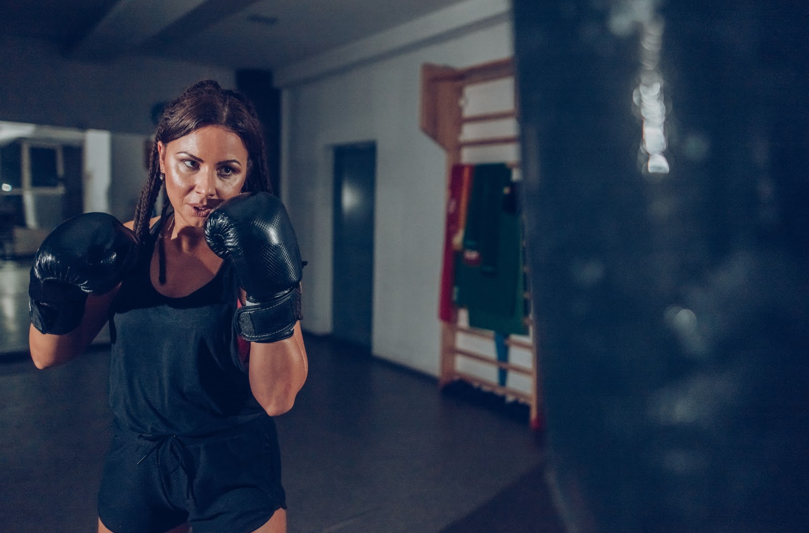 Determined, sweaty woman with black boxing gloves and braids working out on a black heavy bag.
