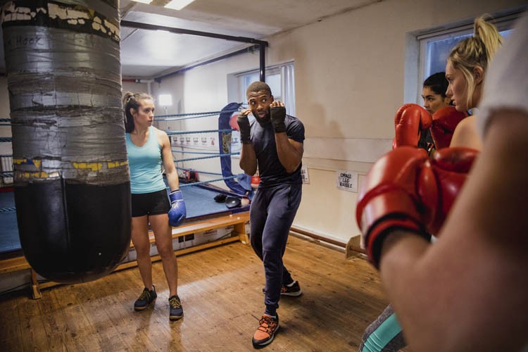 A worn heavy bag with gaffa tape surrounded by boxing instructor and his female pupils.