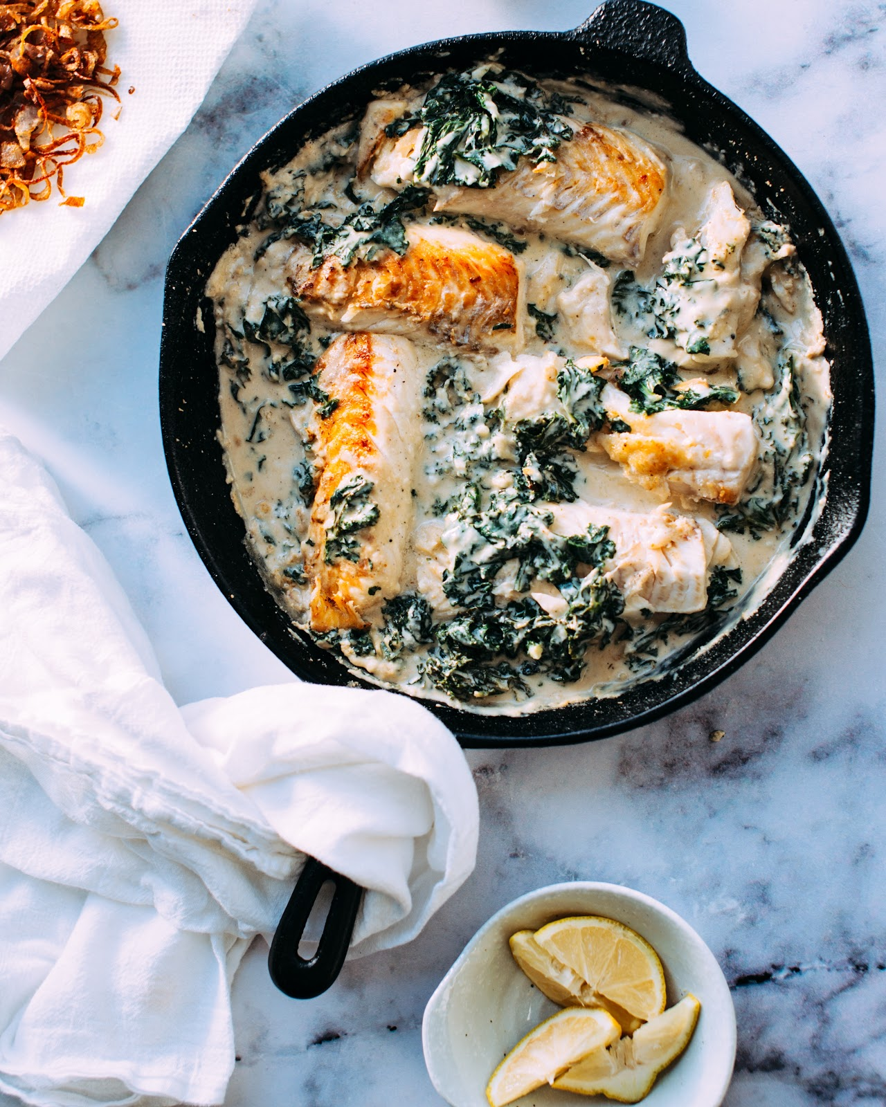 Birds eyes view of creamy salmon dish in skillet with kale and a pot of lemon wedges on the side.
