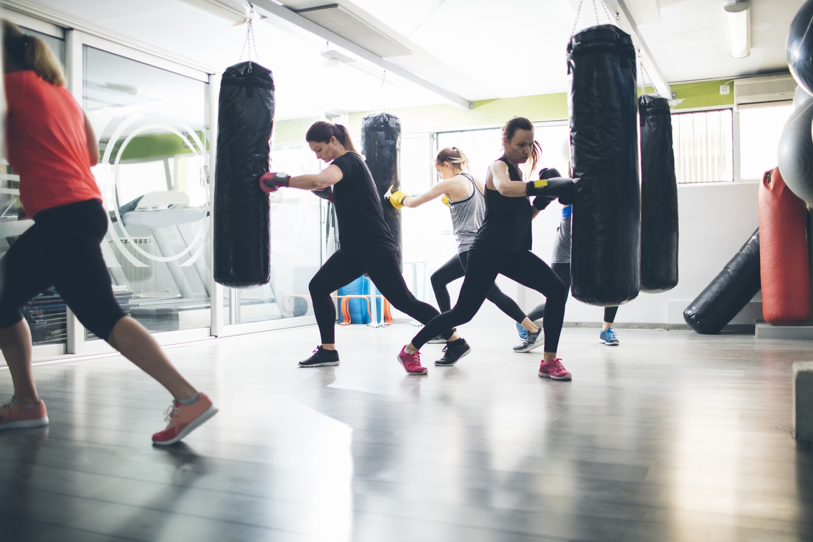 Boxing class with multiple heavy bags suspended from the ceiling and people training hard.
